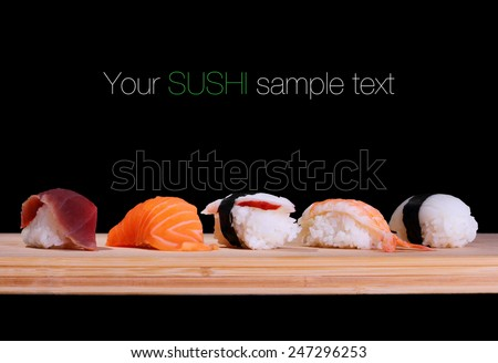 Five species of fish sushi on bamboo board, text space - stock photo
