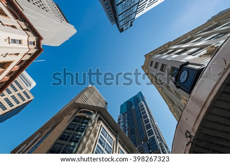Five tall buildings viewed from bottom looking up with blue sky during the day - stock photo