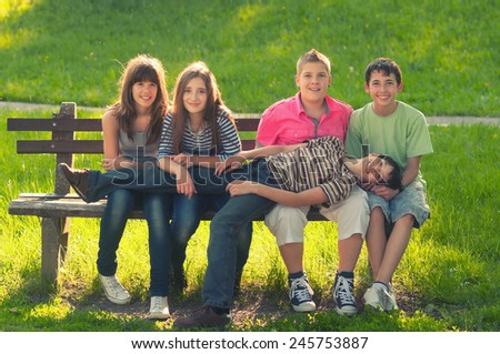 Five teenage boys and girls having fun in the park on sunny spring day. - stock photo