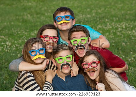 Five teenage male and females in mustache disguise - stock photo