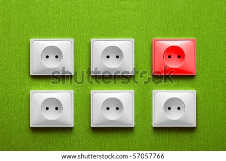 Five white and one red electric sockets in a green wall - stock photo