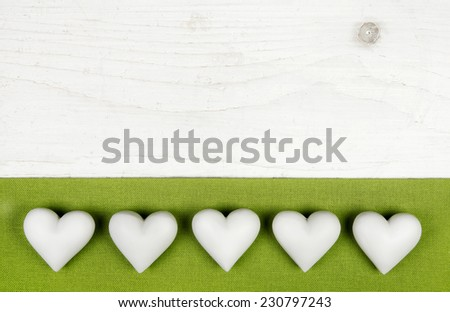 Five white hearts on wooden white shabby chic background with apple green frame. - stock photo