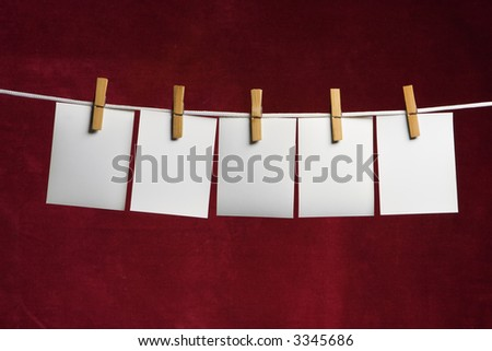 five white slip of paper attach to rope clothes peg on red - stock photo