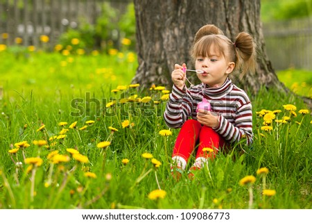 Five-year funny girl blowing soap bubbles in the park - stock photo