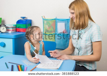 Five-year girl tutor shows the completed task on a sheet - stock photo