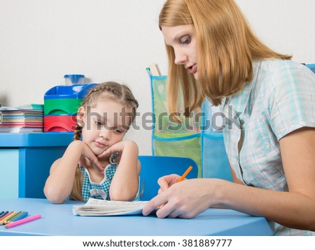 Five-year girl with interest looking notebook and listening to the explanation of the teacher - stock photo
