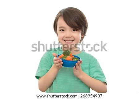 Five year old boy holding bowl of healthy food, isolated on white background. Smiling six year old child with vegetables, broccoli and carrots. Elementary school wellness and healthy eating concept. - stock photo