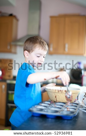 five year old boy making chocolate cakes - stock photo