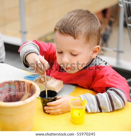 five year old boy painting a toy car - stock photo