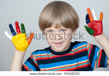 Five year old boy with hands painted in colorful paints ready for hand prints - stock photo