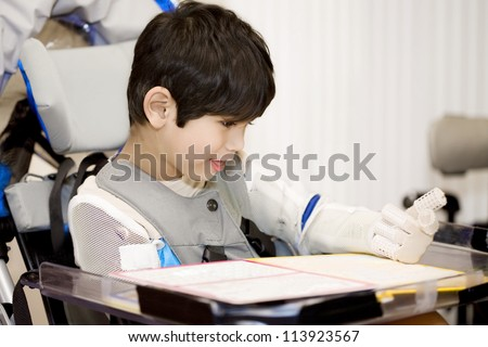 Five year old disabled boy studying in wheelchair - stock photo