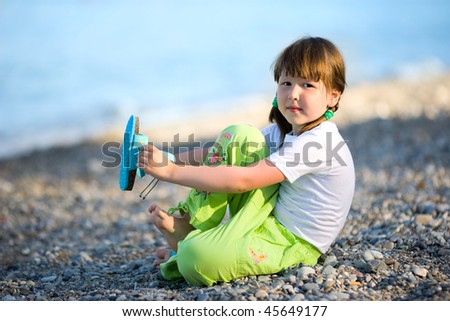Five years Girl sitting on beach putting on shoe - stock photo