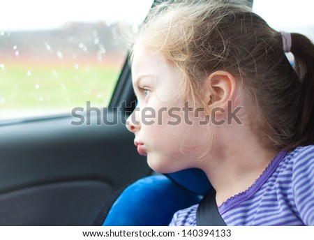 Five years old blond caucasian child girl looking out the window while traveling in a car seat - stock photo