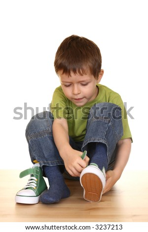 five years old boy tries to put on his sneakers isolated on white - stock photo