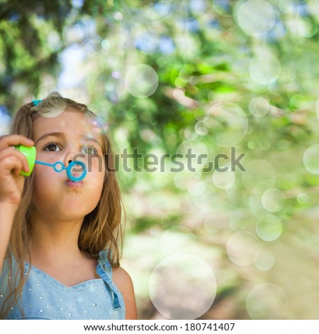 Five years old caucasian child girl blowing soap bubbles outdoor at summer park - happy carefree childhood - stock photo