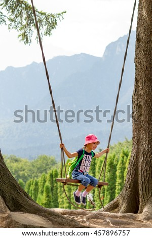 Five years old girl playing on a swing between two giant fir trees with mountains behind. - stock photo