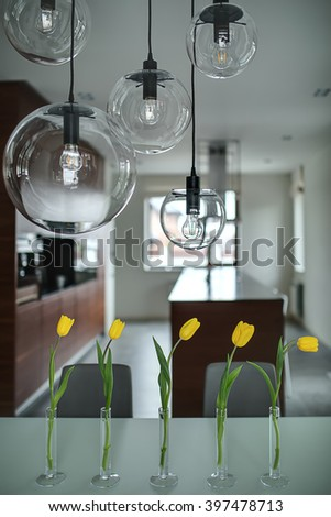 Five yellow tulips in glass vases on the table and five glass round lamps over them. They are on the soft background of brown kitchen with light walls. Vertical. - stock photo