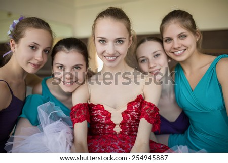 Five young ballerinas sitting on the floor and looking to the camera with smiles. Odeby models in colorful clothes. Point shooting from above. ��¡lose-up portrait. - stock photo