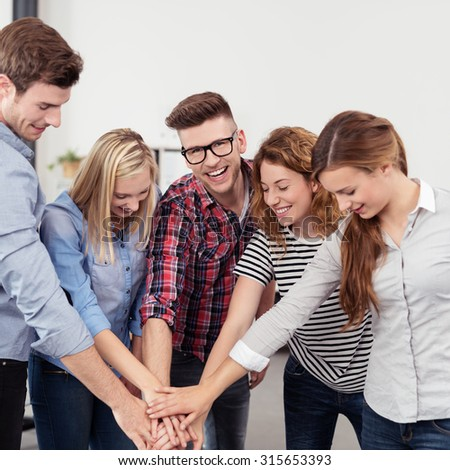 Five Young Happy Office People Putting their Hands on Top of One Another Inside the Office. - stock photo