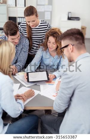 Five Young Office People Looking at the Tablet Screen with Copy Space Together While Having a Meeting Inside the Boardroom. - stock photo