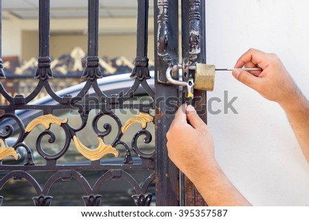 fix lock and key with locksmith on old blue steel door - stock photo