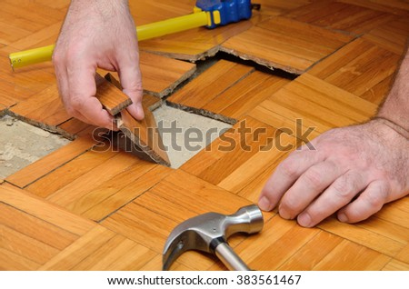 Fixing wooden parquet damaged by moisture or water - stock photo