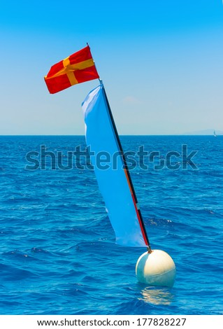 Flag in the sea pointing the finish line in a classic sailing boats regatta in Spetses island in Greece - stock photo