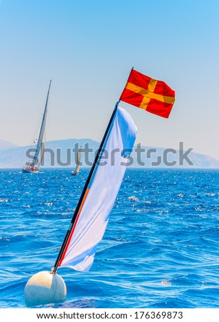 Flag in the sea pointing the finish line in a classic sailng boats regatta in Spetses island in Greece - stock photo
