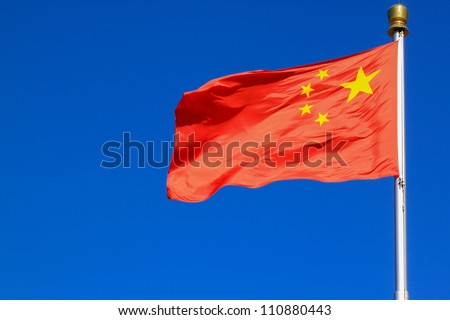 Flag of China against blue sky. - stock photo