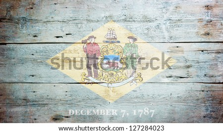 Flag of Delaware painted on grungy wooden background - stock photo