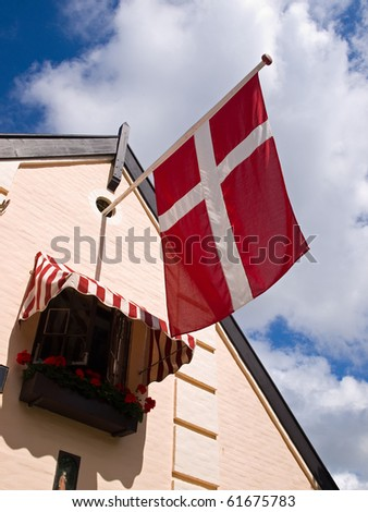 Flag of Denmark Danish on a house with blue sky background - stock photo