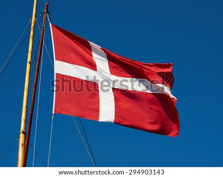 Flag of Denmark up high in the air with clear blue sky background       - stock photo