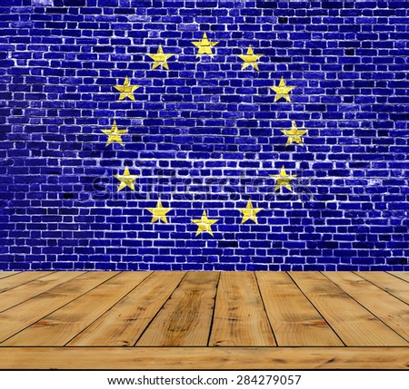 Flag of European Union painted on brick wall with wooden floor inside - stock photo
