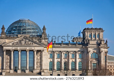 Flag of Federal Republic of Germany waving in front of the German parliament building (Reichstag) in Berlin, Germany - stock photo