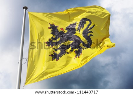 Flag of Flanders (part of Belgium) waving against a dramatic cloudy sky - stock photo
