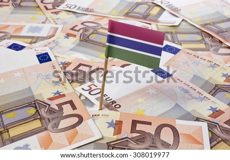 Flag of Gambia sticking in european banknotes.(series) - stock photo