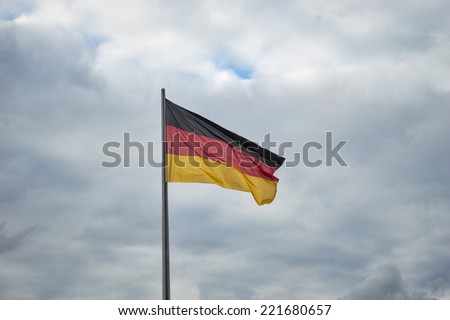 Flag of Germany over a stormy sky - stock photo
