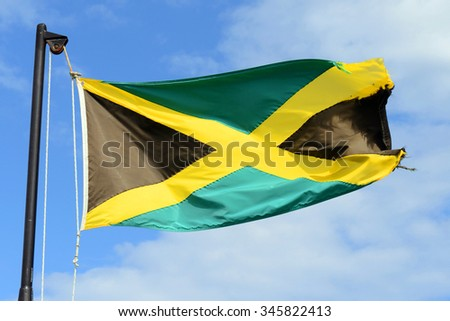 Flag of Jamaica waving against blue sky. Flag of Jamaica have a gold saltire on a green and black field. - stock photo