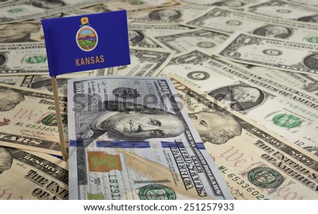 Flag of Kansas sticking in a variety of american banknotes.(series) - stock photo