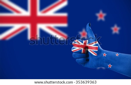 Flag of New Zeland on female's hand, second, defocused flag in background - stock photo