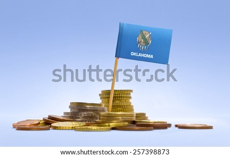 Flag of Oklahoma in a mixed stack of european coins and a blue background.(series) - stock photo