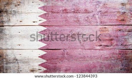Flag of Qatar painted on grungy wood plank background - stock photo