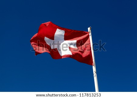 Flag of Switzerland is waving on the sky background - stock photo