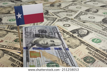 Flag of Texas sticking in a variety of american banknotes.(series) - stock photo