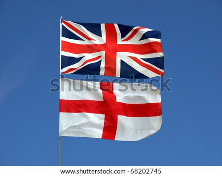Flag of the UK (Union Jack) and flag of England over a blue sky - stock photo