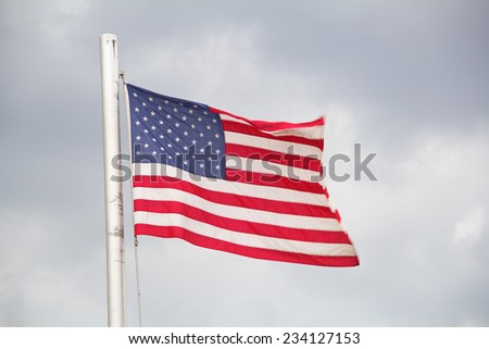Flag of the United States against dark cloudy sky - stock photo