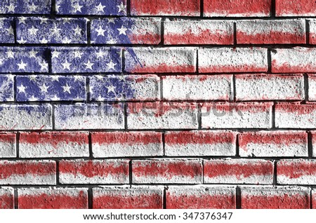 Flag of the United States of America painted onto a grunge brick wall. USA flag. - stock photo