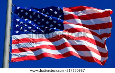 Flag of the USA against a blue sky  - stock photo