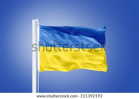 Flag of Ukraine flying against a blue sky. - stock photo
