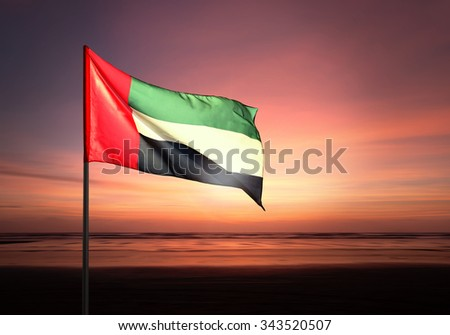 Flag of United Arab Emirates flying against beautiful morning sky. UAE celebrates national day on December 2. - stock photo